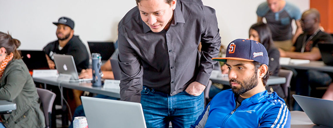 Instructor pointing out material on a student's laptop